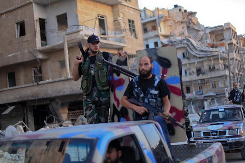 Armed rebel fighters from the Islamic Front drive their pickups on July 19, 2014 in the northern city of Aleppo (AFP Photo/Ahmed Deeb)