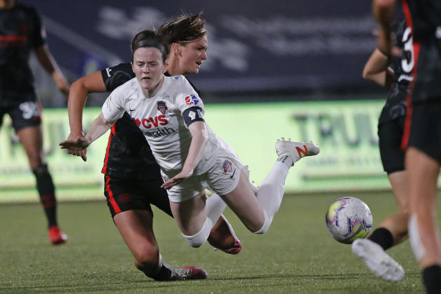 Portland Thorns midfielder Lindsey Horan, left, tackles Washington Spirit midfielder Rose Lavelle during the second half of an NWSL Challenge Cup soccer match at Zions Bank Stadium on Sunday, July 5, 2020, in Herriman, Utah. (AP Photo/Rick Bowmer)
