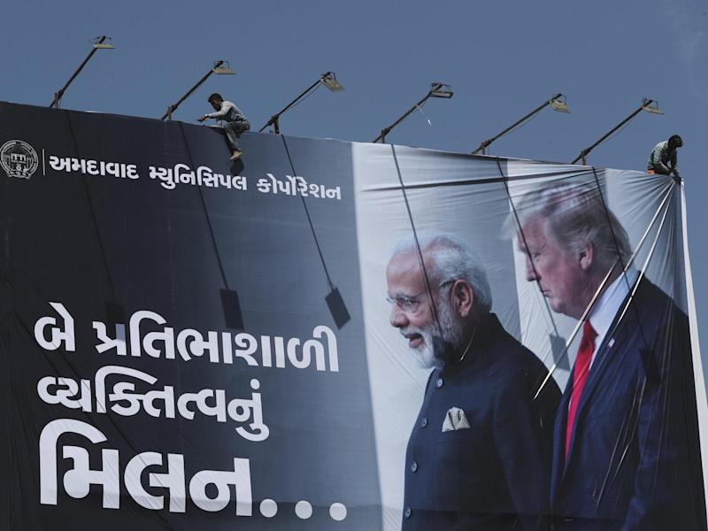 An Indian worker installs a giant hoarding welcoming US President Donald Trump ahead of his visit, in Ahmadabad, India: AP