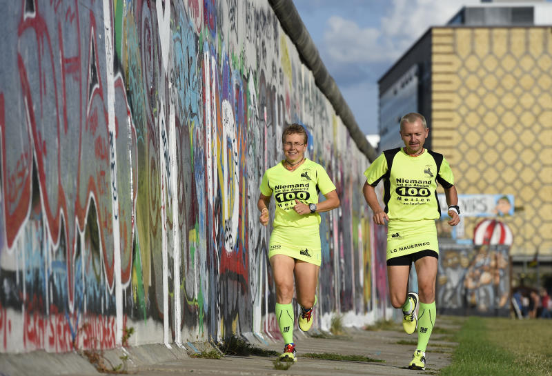 """Martina Schliep and her partner Gaston Pruefer run along the old Berlin Wall on August 11, 2014 as they train before taking part in the """"100MeilenBerlin"""" marathon event"""