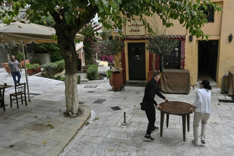 Employees remove the last tables from a terrace of a restaurant in Plaka district of central Athens as cafes, bars and restaurants close due to a partial lockdown to stem the spread of the novel coronavirus