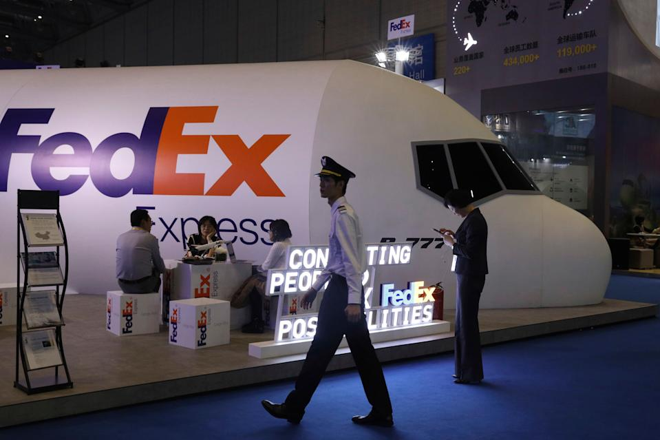 A man dressed as a pilot walks past the FedEx booth during the China International Import Expo in Shanghai, Monday, Nov. 5, 2018. Chinese President Xi Jinping has promised to open China's market wider as he opened a trade fair meant to promote the country's image as an importer, but he offered no response to U.S. and European complaints about technology policy and curbs on foreign business. (AP Photo/Ng Han Guan)
