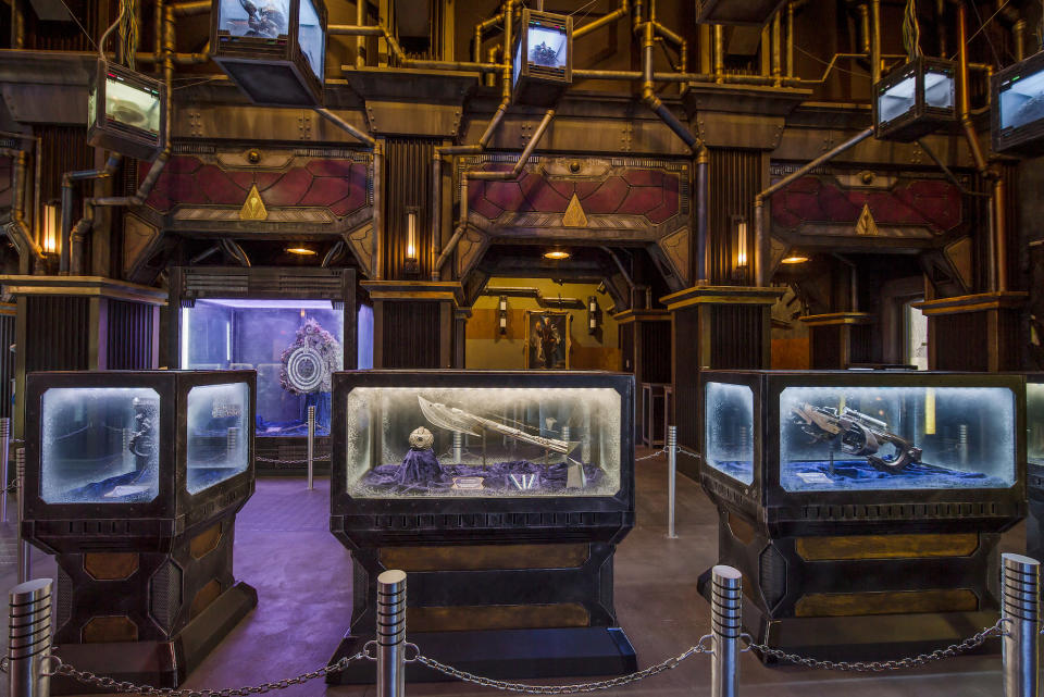 <p>The Collector apparently has a thing for film props: His gallery includes cases filled with the artifacts of the Kree (center; an orb and a blade similar to the weapon wielded by Ronan the Accuser in the first <em>Guardians</em>) and Chitauri (right; the energy gun used against Earth's Mightiest in the first <em>Avengers</em>). (Photo: Disneyland Resort) </p>