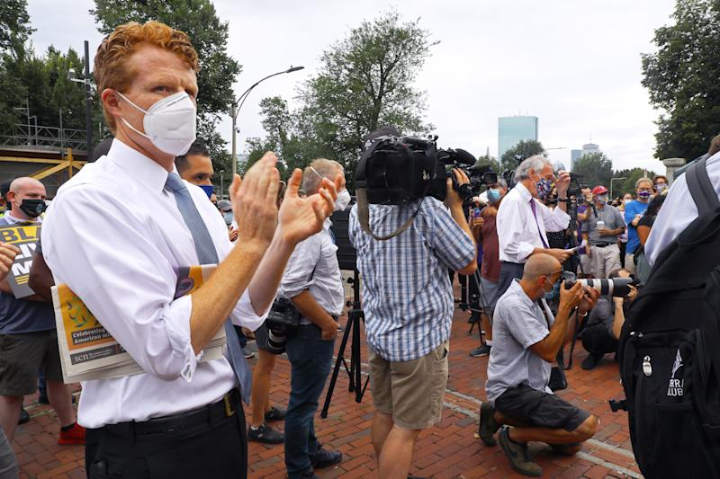 "Rep. Joe Kennedy III, left, listens as Sen. Ed Markey, right, speaks at an SEIU rally at the State House in Boston on ""a day of reckoning"" for Black Lives on July 20, 2020. (Pat Greenhouse/Boston Globe via Getty Images)"