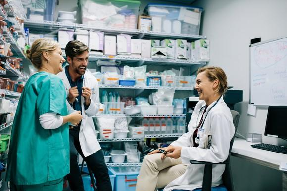 Three healthcare providers laughing while taking a break in the storeroom.