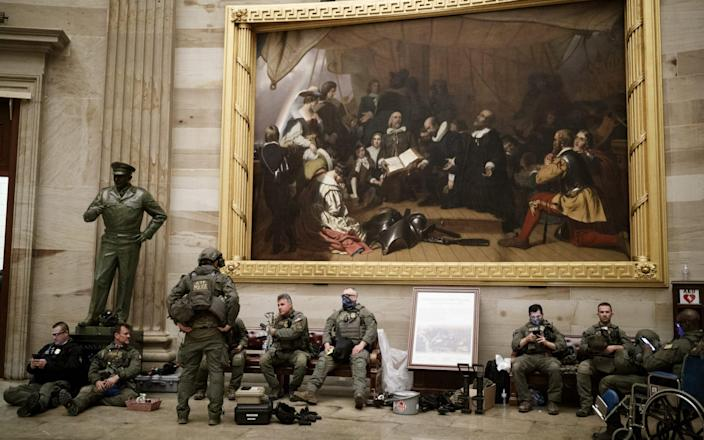Members of law enforcement rest in the U.S. Capitol in Washington D.C., U.S., on Wednesday, Jan. 6 - Bloomberg