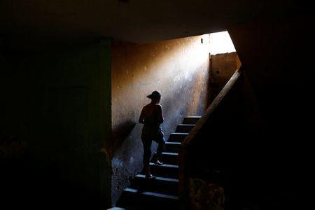 Elizabeth Altuve climbs the stairs at the occupied building where she lives in Maracaibo, Venezuela July 26, 2018. Picture taken July 26, 2018. REUTERS/Marco Bello