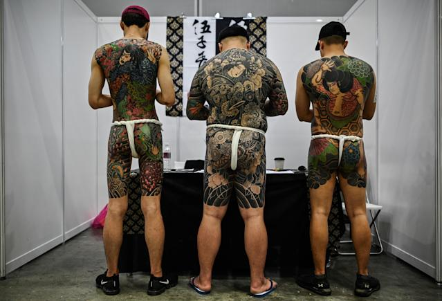 Three men display their tattoos at the expo. (Getty)