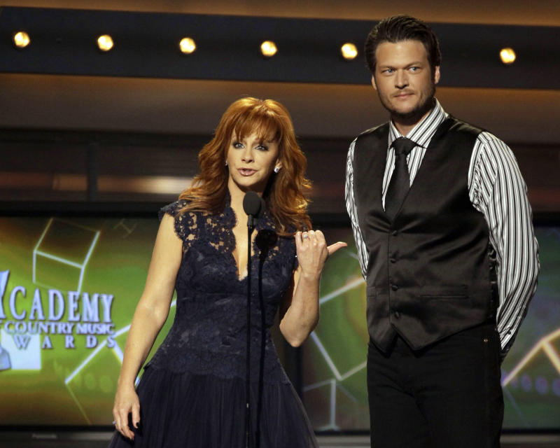 FILE - This April 3, 2011 file photo shows hosts Reba McEntire, left, and Blake Shelton onstage at the 46th Annual Academy of Country Music Awards in Las Vegas. McEntire is ending her run as host of the Academy of Country Music Awards. She's stepping aside after a record 14 appearances, the last two with co-host Blake Shelton, who will return on the 2013 edition of the awards show. (AP Photo/Julie Jacobson, file)