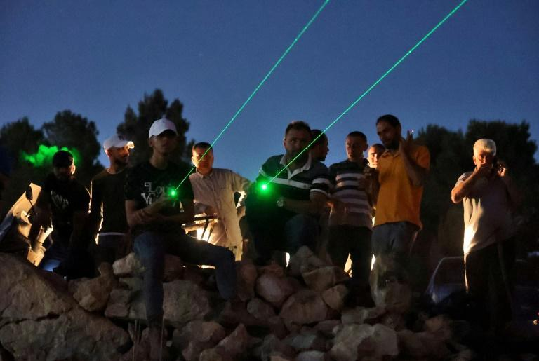 Palestinian protesters use laser torches during a demonstration against the Israeli settler outpost of Eviatar on June 28, 2021