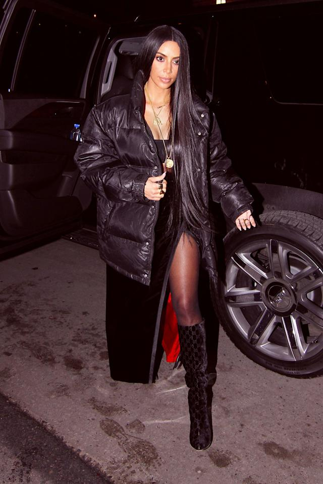 <p><span>In a black puffer jacket, bandeau top, thigh-high slit velvet skirt with bright red lining, black tights and checkered knee-high boots while out to dinner at Carbone in NYC with Kanye West.</span><span></span></p>