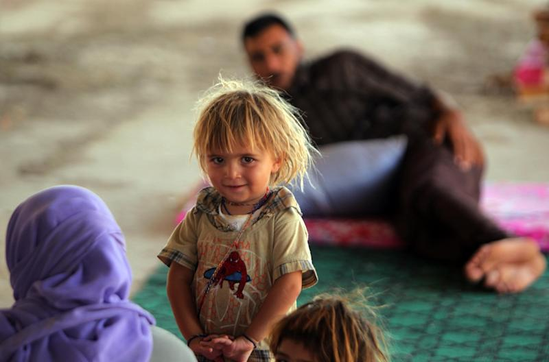 An Iraqi Yazidi girl, who fled her home with her family when Islamic State (IS) militants attacked the town of Sinjar, stands inside a building under construction on the outskirts of the Kurdish city of Dohuk, on August 16, 2014