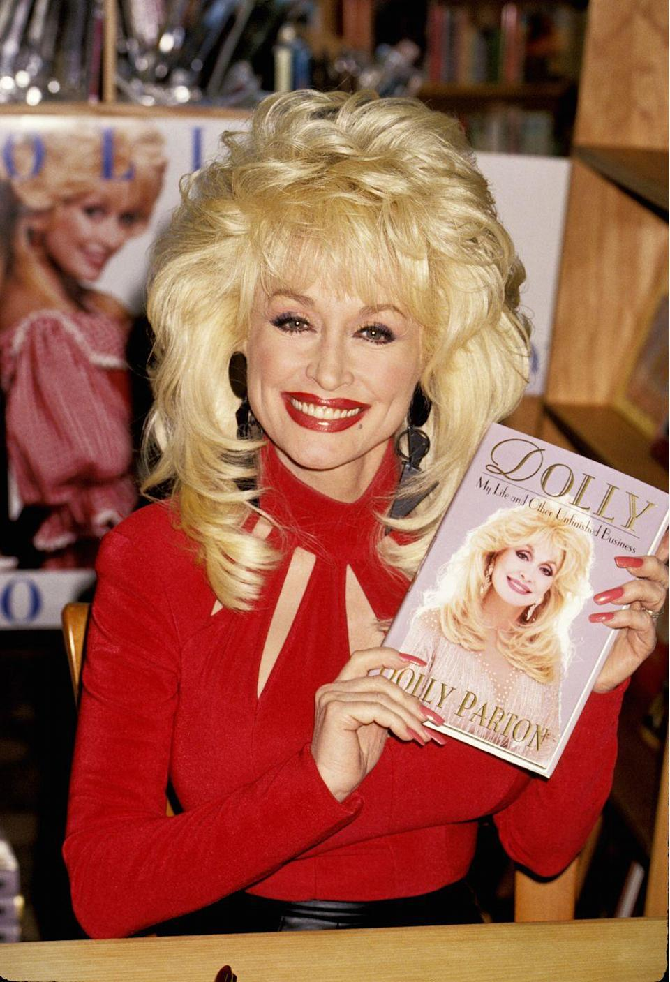 """<p>Dolly signings her memoir <em><a href=""""https://www.amazon.com/Dolly-Life-Other-Unfinished-Business/dp/0061092363?tag=syn-yahoo-20&ascsubtag=%5Bartid%7C1782.g.35034126%5Bsrc%7Cyahoo-us"""" rel=""""nofollow noopener"""" target=""""_blank"""" data-ylk=""""slk:Dolly: My Life and Other Unfinished Business"""" class=""""link rapid-noclick-resp"""">Dolly: My Life and Other Unfinished Business</a>.</em></p>"""