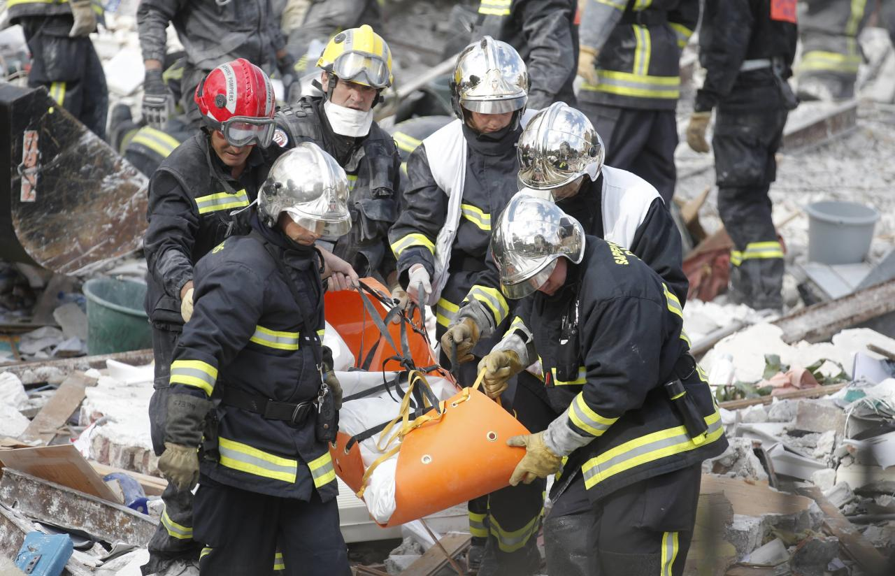 Firefighters carry a body on a stretcher from the rubble of a collapsed building in Rosny-Sous-Bois, near Paris, August 31, 2014. The four-storey building in a Paris suburb collapsed after an explosion on Sunday morning, killing a child and an elderly woman, and emergency teams were searching the rubble for others still missing. REUTERS/Christian Hartmann (FRANCE - Tags: DISASTER)
