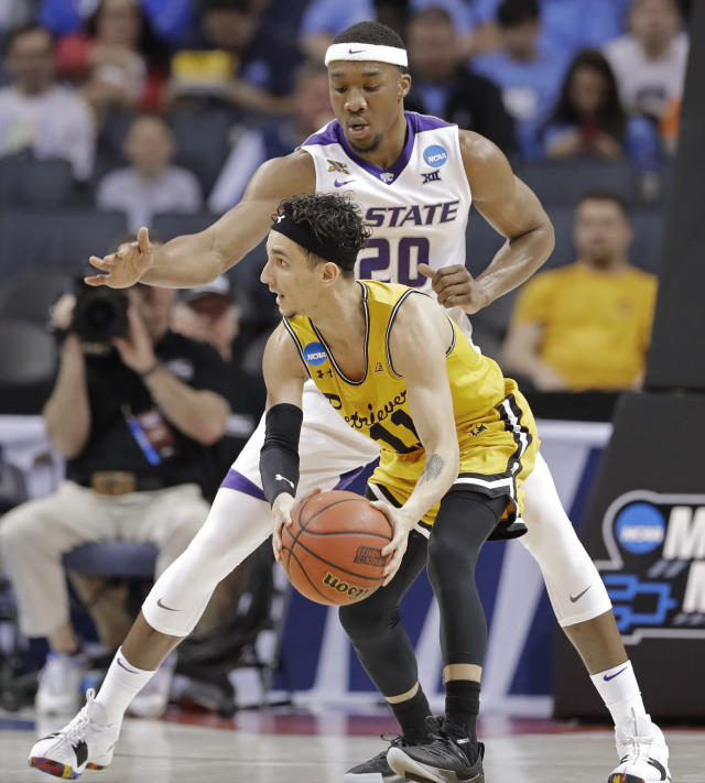 Kansas State's Xavier Sneed (20) guards against UMBC's K.J. Maura (11) during the first half of a second-round game in the NCAA men's college basketball tournament in Charlotte, N.C., Sunday, March 18, 2018. (AP Photo/Gerry Broome)