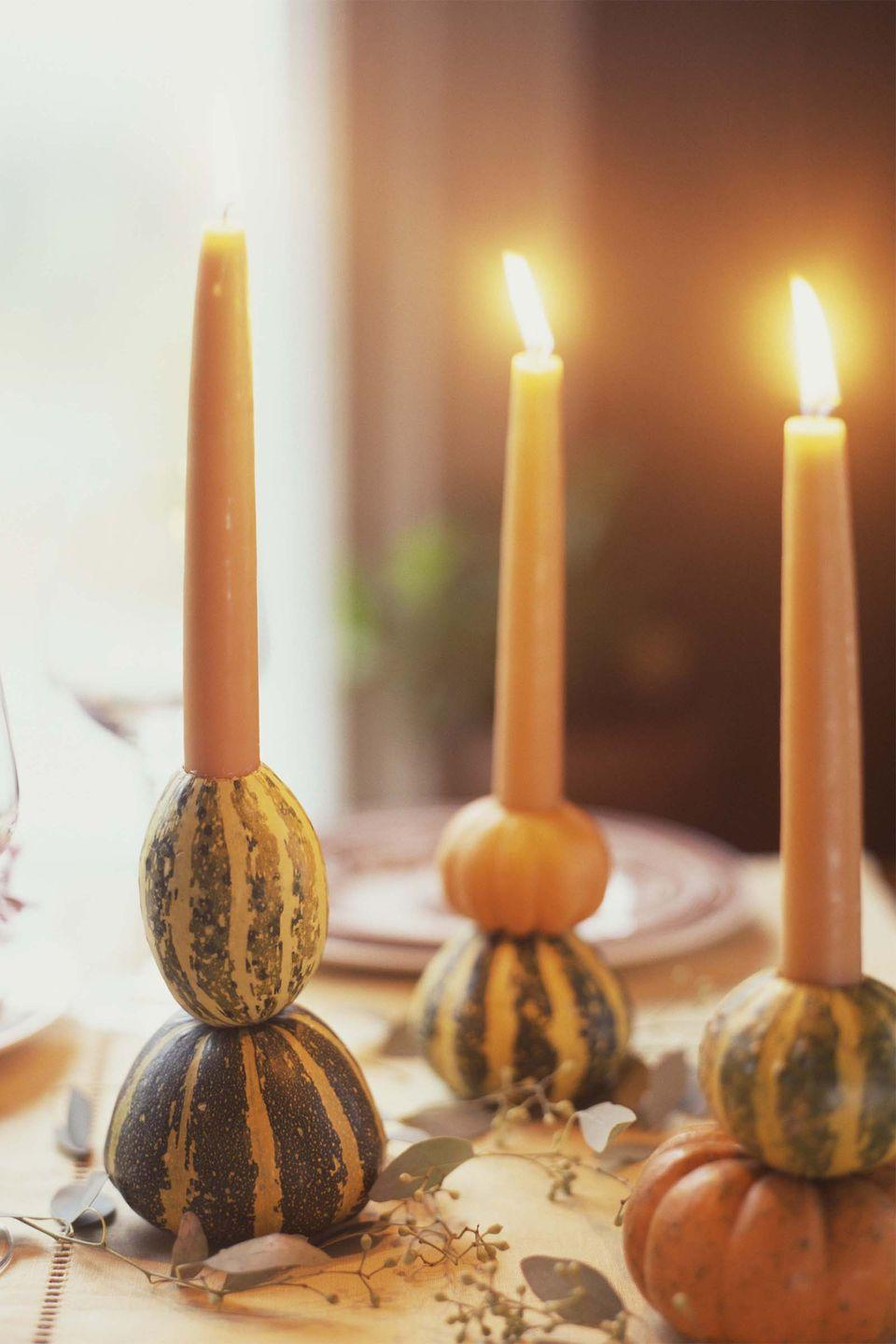 """<p>Hollow out the middle of a couple miniature gourds and pumpkins, then slide in a taper candle for a seasonal DIY candlestick.</p><p><a class=""""link rapid-noclick-resp"""" href=""""https://www.amazon.com/Higlow-Dripless-Candles-Wedding-Decoration/dp/B01MXDKJ5F?tag=syn-yahoo-20&ascsubtag=%5Bartid%7C10050.g.1371%5Bsrc%7Cyahoo-us"""" rel=""""nofollow noopener"""" target=""""_blank"""" data-ylk=""""slk:SHOP CANDLES"""">SHOP CANDLES</a></p>"""