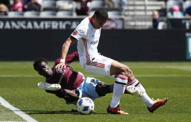Toronto FC midfielder Ryan Telfer, front, gets tangled up with Colorado Rapids forward Dominique Badji as they fight for control of the ball in the first half of an MLS soccer match Saturday, April 14, 2018, in Commerce City, Colo. (AP Photo/David Zalubowski)