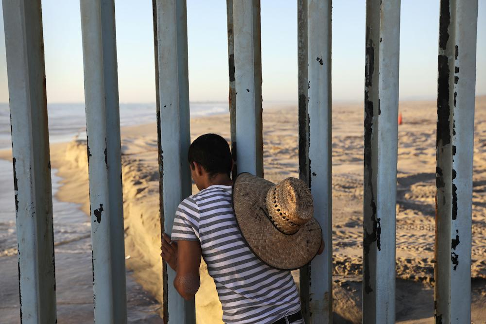 <p>In Tijuana, Mexico, a man looks through the U.S.-Mexico border fence into the United States on Sept. 25, 2016. The binational Friendship Park is one of the few places along the 2,000-mile border where separated families are allowed to meet. (Photo: John Moore/Getty Images) </p>