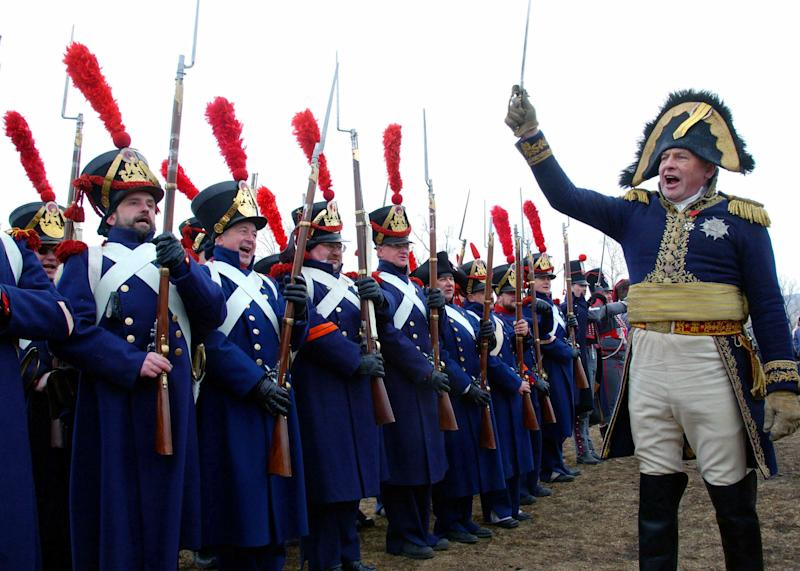 Oleg Sokolov (R), president of the military-historical association of Russia who is dressed as French emperor Napoleon Bonaparte, welcomes members of the Krasnoyarsk society of fans of the military history sporting the uniforms of French naval gunners during a show in a park in the Siberian city of Krasnoyarsk, April 10, 2005. The members of the clubs from major Siberian cities - Krasnoyarsk, [Novosibirsk, Tomsk and Irkutsk], took part on Sunday in the first Siberian regional festival of clubs of military-historical reconstruction.