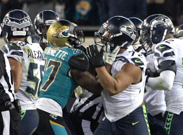 Jacksonville running back Leonard Fournette (27) and Seattle defensive end Michael Bennett (72) shove each other during a scrum between the two teams near the end of the game after Bennett rolled into the knees of a Jaguars player. (AP)