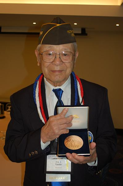 In this Nov. 2011 photo provided by Irene Tanabe, Frank Tanabe holds a replica of the Congressional Gold Medal in Washington, D.C., awarded collectively to Japanese-American veterans of World War II, including those who served in his unit, the Military Intelligence Service. A photograph of a 93-year-old World War II veteran casting what will likely be his last ballot has captured the hearts of tens of thousands of Internet users. (AP Photo/Irene Tanabe)