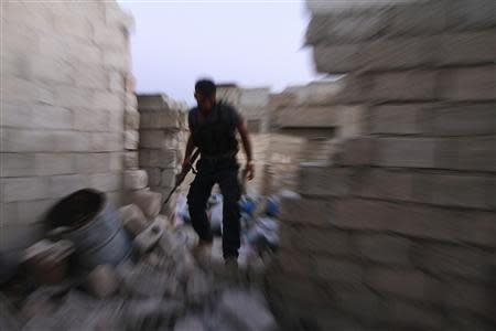 A Free Syrian Army fighter walks on the rubble of damaged buildings near Nairab military airport in Aleppo