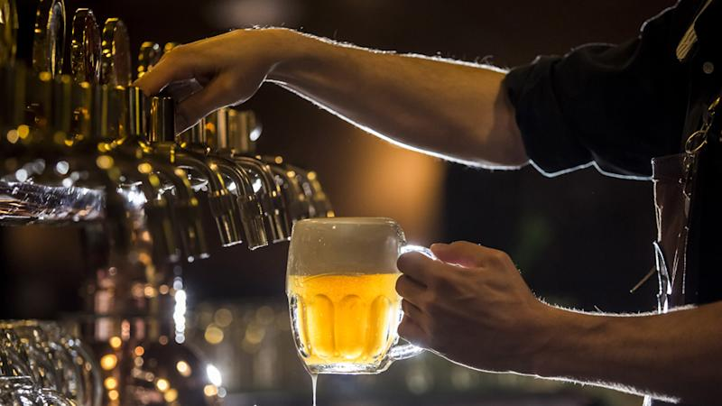 A getty stock image of a person pouring a beer from a pub