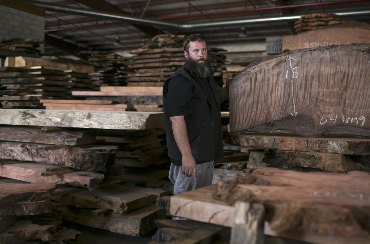 Landon Buck, owner of Redwood Burl Inc., looks on at the warehouse in Arcata, California June 13, 2014. Most of the shop's wood was cut more than 50 years ago and bought from private landowners. Picture taken June 13, 2014. REUTERS/Nick Adams (UNITED STATES - Tags: BUSINESS)