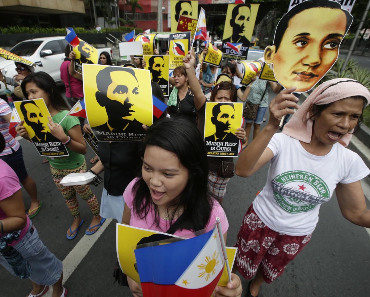Protesters display placards showing national hero Apolinario Mabini, while shouting slogans outside the Chinese Consulate at the financial district of Makati city east of Manila Thursday, June 12, 2014, during a rally against recent reclamation and construction at Mabini Reef in the disputed Spratlys group of islands in the South China Sea. The protesters, who are allied with Philippine President Benigno Aquino III, marked the country's Independence Day Thursday, with a protest rally against China's aggressive moves to reclaim land in the South China Sea where the two countries are locked in an escalating territorial dispute. (AP Photo/Bullit Marquez)