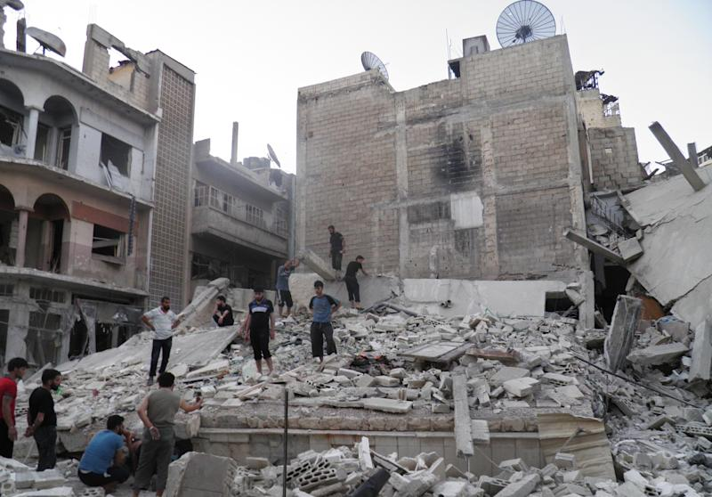 This citizen journalism image provided by Shaam News Network SNN, taken on Saturday, Aug. 11, 2012, purports to show Syrians standing in the rubble of a destroyed building from Syrian forces shelling in Khaldiyeh neighborhood, Homs province, central Syria. (AP Photo/Shaam News Network, SNN)THE ASSOCIATED PRESS IS UNABLE TO INDEPENDENTLY VERIFY THE AUTHENTICITY, CONTENT, LOCATION OR DATE OF THIS CITIZEN JOURNALIST IMAGE