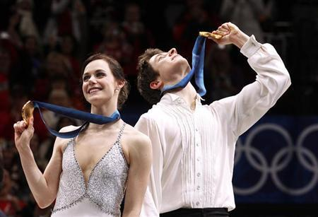 Canada's Tessa Virtue (L) and Scott Moir hold up their gold medals during the medals ceremony for the ice dance figure skating event at the Vancouver Winter Olympics February 22, 2010. REUTERS/Lucy Nicholson