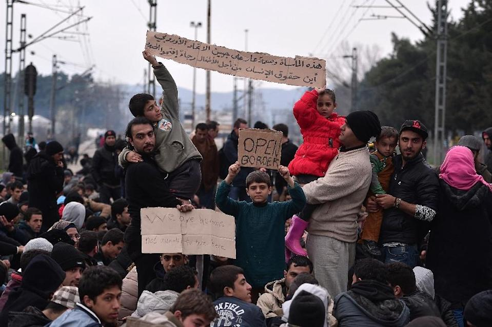 """Syrian and Iraqi refugees trapped at the Greek-Macedonian border demonstrate, shouting """"open the border"""" as they block the train tracks on February 28, 2016 (AFP Photo/Louisa Gouliamaki)"""
