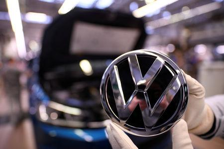 FILE PHOTO: An employee holds a Volkswagen logo in a production line at the Volkswagen plant in Wolfsburg, Germany March 1, 2019.  REUTERS/Fabian Bimmer/File Photo