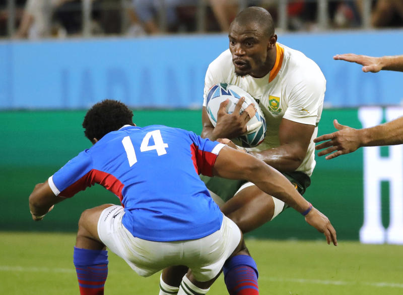 South Africa's Makazole Mapimpi runs at the Namibia's Chad Plato, left, during the Rugby World Cup Pool B game at the City of Toyota Stadium between South Africa and Namibia in Toyota City, Japan, Saturday, Sept. 28, 2019. (AP Photo/Christophe Ena)
