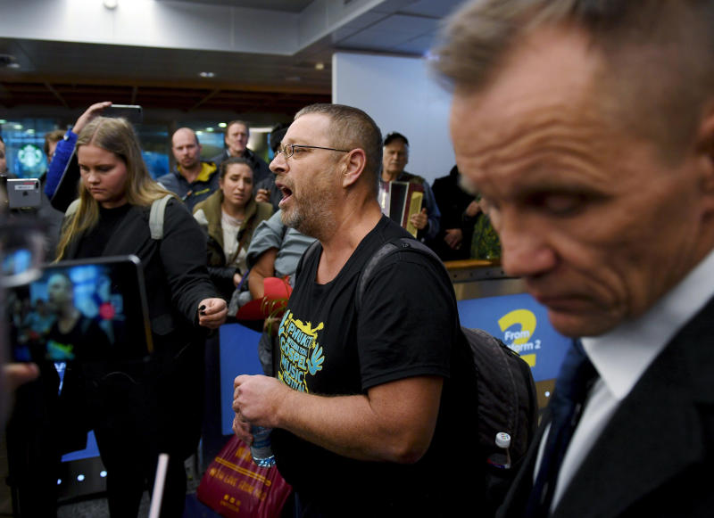 Spokesman and group leader Timo Valtonen, center, makes a statement to the press upon his arrival, with three other Finns after being deported from Malaysia, at the airport in Vantaa, Finland, Wednesday, Nov. 28, 2018. Four Finnish tourists who were arrested in Malaysia last week for distributing Christian materials in public places on a resort island have returned to Finland. (Antti Aimo-Koivisto/Lehtikuva via AP)