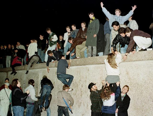 People climb the Berlin wall at the Brandenburg Gate as they celebrate the opening of the East German border November 9, 1989. Credit: Reuters/Herbert Knosowski