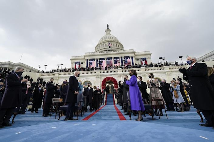 Kamala Harris applauds as Joe Biden arrives for his inauguration with people and the U.S. Capitol in the background.
