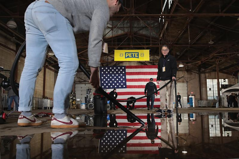 Workers clean up water from a leaking roof before the start of a rally where South Bend Mayor Pete Buttigieg announced that he will be seeking the Democratic nomination for president in the old Studebaker car factory on April 14, 2019 in South Bend, Indiana.