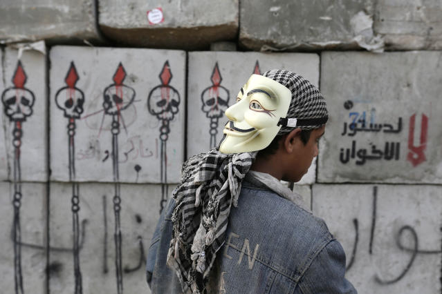 "A protester looks at graffiti on cement blocks in front of the presidential palace in Cairo, Egypt, Sunday, Dec. 16, 2012. Key Egyptian rights groups called Sunday for a repeat of the first round of the constitutional referendum, alleging the vote was marred by widespread violations. Islamists who back the disputed charter claimed they were in the lead with a majority of ""yes"" votes. Arabic writing on the cement block, right, reads, ""no to the Muslim Brotherhood constitution,"" (AP Photo/Hassan Ammar)"