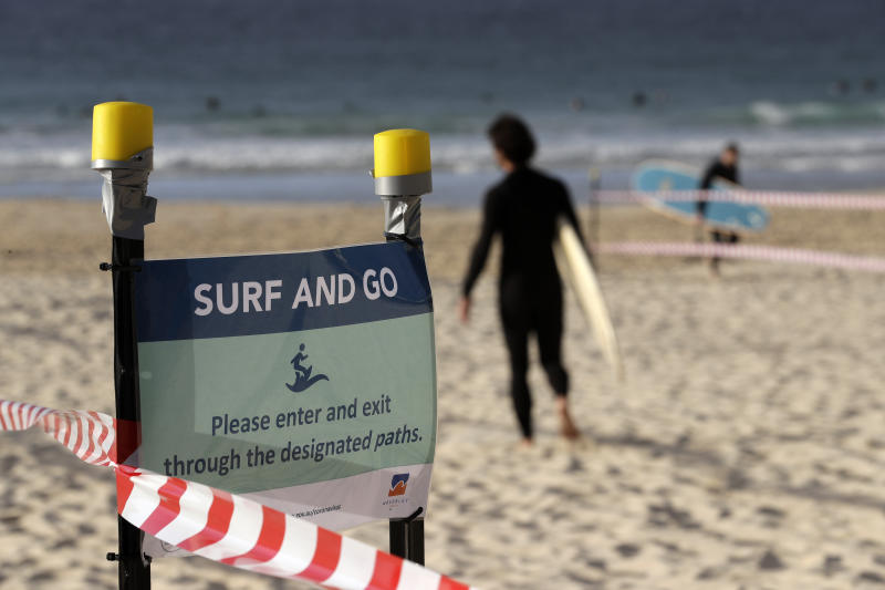A sign tells surfers to leave once they have finished surfing at Bondi Beach in Sydney, Tuesday, April 28, 2020, as coronavirus pandemic restrictions are eased. The beach is open to swimmers and surfers to exercise only. (AP Photo/Rick Rycroft)