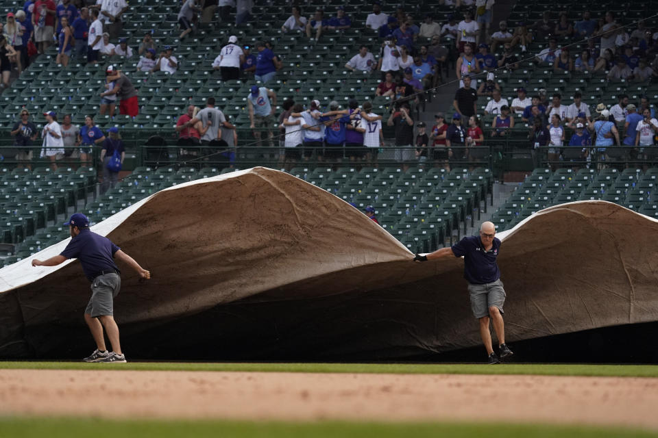 The grounds crew cover the field with a tarp during a rain delay in the ninth inning of a baseball game between the Arizona Diamondbacks and the Chicago Cubs in Chicago, Saturday, July 24, 2021. (AP Photo/Nam Y. Huh)