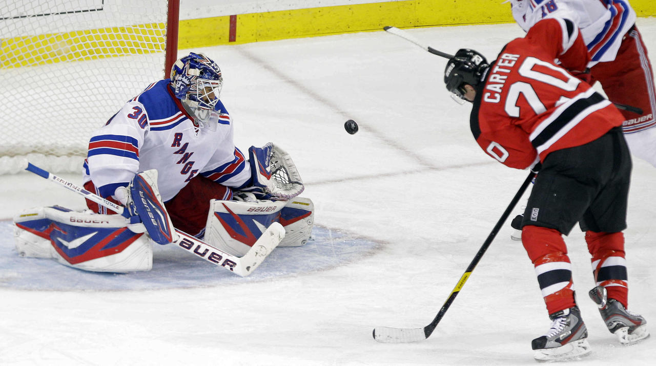 New York Rangers goalie Henrik Lundqvist (30), of Sweden, stops a shot on the goal by New Jersey Devils' Ryan Carter (20) during the third period of game 3 of an NHL hockey Stanley Cup Eastern Conference final playoff series Saturday, May 19, 2012, in Newark, N.J. (AP Photo/Frank Franklin II)
