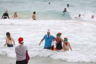 People wearing Christmas-themed attire pose for photos on Christmas Day at Bondi Beach in Sydney