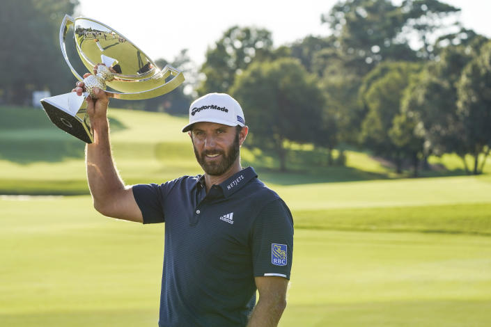 Dustin Johnson celebrates with the FedEx Cup trophy after winning the Tour Championship golf tournament on Monday, Sept. 7, 2020 at Lake Golf Club in Atlanta. (AP Photo/John Bazemore)