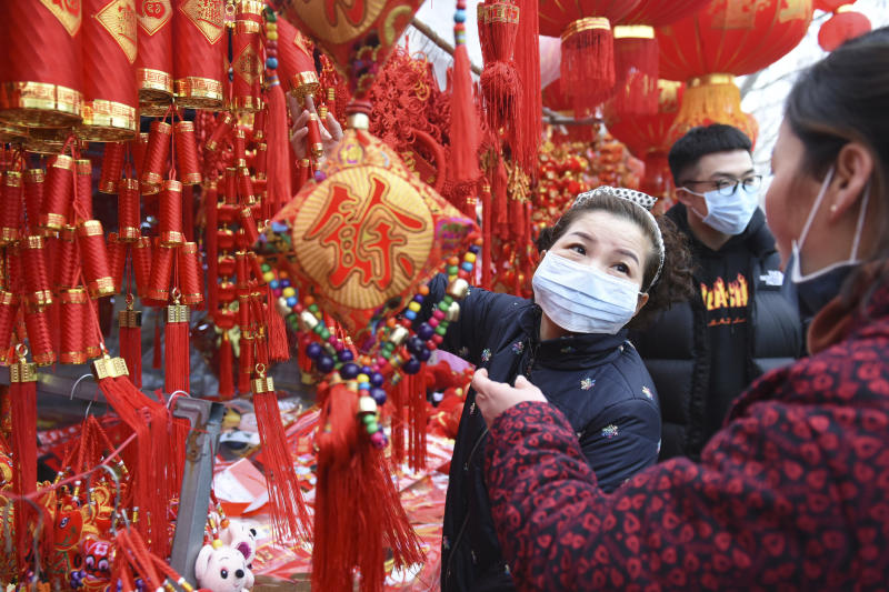 People wear face masks as they shop for decorations for the upcoming Lunar New Year, the Year of the Rat, at a market in Fuyang in central China's Anhui Province, Friday, Jan. 24, 2020. China is swiftly building a hospital dedicated to treating patients infected with a new virus that has killed 26 people, sickened hundreds and prompted unprecedented lockdowns of cities home to millions of people during the country's most important holiday. (Chinatopix via AP)