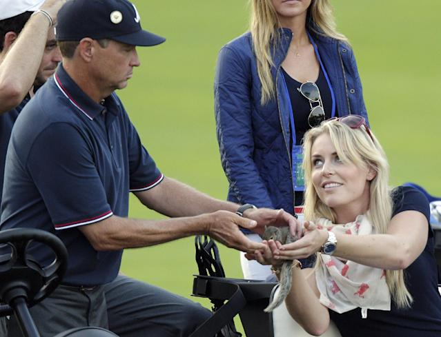 Lindsey Vonn, right, girlfriend of the United States' Tiger Woods, hands a small squirrel to Davis Love III while they watch the last four-ball match of the day at the Presidents Cup golf tournament at Muirfield Village Golf Club Thursday, Oct. 3, 2013, in Dublin, Ohio. Davis Love III found the squirrel earlier in the day and has kept in his cart during the matches. (AP Photo/Jay LaPrete)
