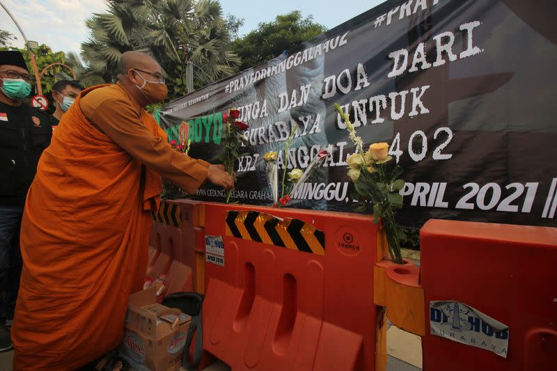 A monk puts flowers during a prayer for the missing Indonesian Navy KRI Nanggala-402 submarine in Surabaya