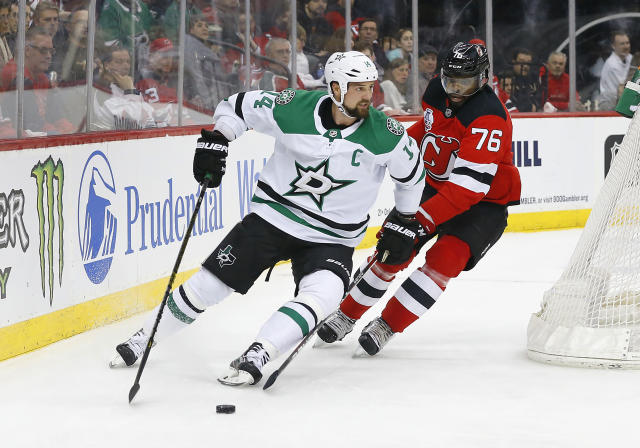 Dallas Stars left wing Jamie Benn (14) plays the puck against New Jersey Devils defenseman P.K. Subban (76) during the first period of an NHL hockey game Saturday, Feb. 1, 2020, in Newark, N.J. (AP Photo/Noah K. Murray)