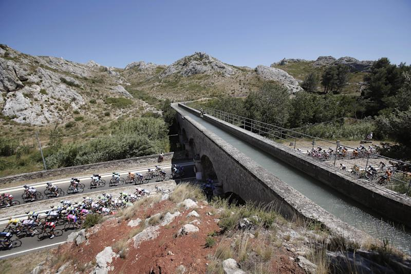 The pack passes under an aqueduct during the sixth stage of the Tour de France cycling race over 176.5 kilometers (110.3 miles) with start in Aix-en-Provence and finish in Montpellier, southern France, Thursday July 4, 2013. (AP Photo/Christophe Ena)