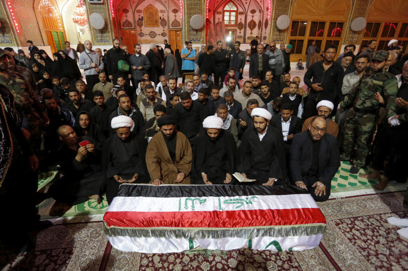 FILE - In this file photo taken Friday, Nov. 29, 2013, mourners pray over the coffin of an Iraqi Shiite fighter, Raed Ali Hussein, during the funeral in the Shiite holy city of Najaf, 100 miles (160 kilometers) south of Baghdad, Iraq. The monthly death toll in Iraq dropped by nearly a third to 659 last month, the U.N. said Sunday, but a recent spike in the number of bullet-riddled bodies found on the street has raised fears the country is facing a return to all-out warfare between Sunni and Shiite factions. (AP Photo, File)